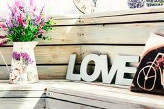 Les fleurs dans un vase avec le mot aiment avec un oreiller avec une photo d'une bicyclette sur le fond des conseils en bois Photo stock
