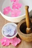 Les fleurs dans une eau roulent avec la bougie et un pilon en bois Photos stock