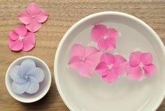 Les fleurs dans une eau roulent pour l'aromatherapy sur un fond en bois Images stock