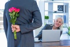 Les fleurs de dissimulation d'homme d'affaires derrière soutiennent pour le collègue photo stock