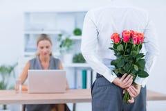 Les fleurs de dissimulation d'homme d'affaires derrière soutiennent pour le collègue photographie stock