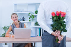 Les fleurs de dissimulation d'homme d'affaires derrière soutiennent pour le collègue photos libres de droits