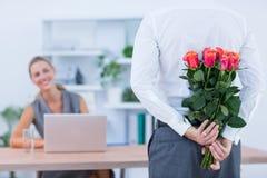 Les fleurs de dissimulation d'homme d'affaires derrière soutiennent pour le collègue Images stock
