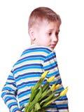 Les fleurs de prise de petit garçon derrière soutiennent Photos libres de droits