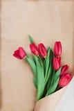Les fleurs de tulipe de ressort enveloppées dans la vue supérieure de papier d'emballage dans l'appartement étendent le style Sal Images stock