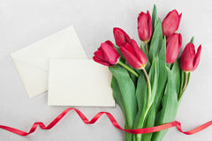 Les fleurs de tulipe de ressort et la carte de papier sur l'appartement en pierre de vue supérieure de table étendent le style Sa Image libre de droits