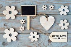 Les fleurs en bois, le coeur, panneau de craie noir et avec le label d'amour sur un gris bleu ont noué le vieux fond en bois avec Image stock