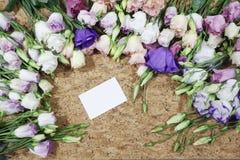 Les fleurs encadrent avec la carte de visite professionnelle de visite sur le fond en bois Photographie stock libre de droits