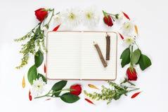 Les fleurs et ouvrent le carnet vide sur le fond blanc Images stock