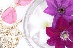 Les fleurs flottent dans l'eau dans un bol en verre, lunettes de soleil roses, la coquille du bébé, photographie stock libre de droits