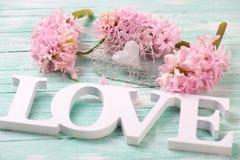 Les fleurs roses de jacinthes, le coeur décoratif et le mot en bois aiment o Photos libres de droits