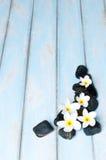 Les fleurs sur le groupe de la pierre noire wooen dessus le plancher Image stock