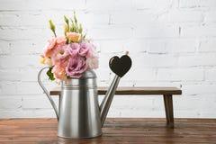 Les fleurs tendres dans la boîte d'arrosage et le petit banc avec le symbole de coeur ont arrangé sur la surface en bois Images stock