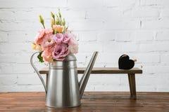 Les fleurs tendres dans la boîte d'arrosage et le petit banc avec le symbole de coeur ont arrangé sur la surface en bois Image stock