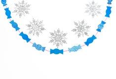 Les flocons de neige scintillants décoratifs et les sucreries de papier sur le blanc ont isolé le fond Images stock