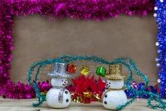 Les flocons de neige sont sur un plancher en bois avec un boîte-cadeau sur la tête Photo libre de droits