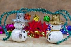 Les flocons de neige sont sur un plancher en bois avec un boîte-cadeau sur la tête Image stock
