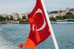Les flottements turcs nationaux de drapeau dans le vent contre le contexte du Bosphorus et d'Istanbul brouillés dans Photos libres de droits