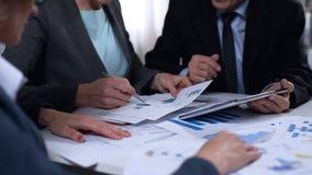 Les fonctionnaires de gouvernement discutant l'importation et l'exportation rapportent des diagrammes, recherche image libre de droits