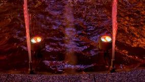 Les fontaines colorées rougeoient la nuit dans la ville Coloré éclabousse et voyage en jet de l'eau sur un fond noir clips vidéos