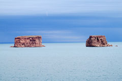 Les formations de roche rouges dans le lac bleu arrosent photographie stock