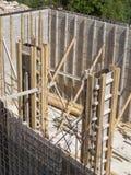Les formes en bois emballent des colonnes de béton armé à un chantier de construction images libres de droits