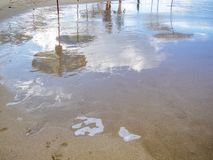 Les formes humaines vagues, les cumulus et les parapluies de plage ont réfléchi sur une surface humide de plage sablonneuse sur l images libres de droits