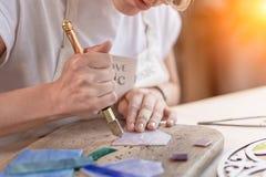 Les formulaires d'artiste du verre souillé dans la petite mosaïque ajuste Plan rapproché photographie stock libre de droits