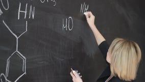 Les formules d'écriture de professeur sur le conseil de craie et explique les étudiants la formule banque de vidéos