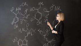 Les formules d'écriture de professeur sur le conseil de craie et explique les étudiants la formule clips vidéos
