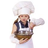 Les fouets de cuisinière de petite fille battent des oeufs dans un grand plat Photographie stock