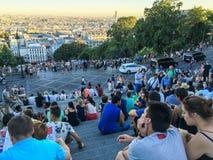 Les foules des touristes s'asseyent sur des escaliers de Sacre Coeur et l'horizon de vue de Paris de Montmartre Photographie stock
