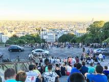 Les foules des touristes s'asseyent sur des escaliers de Sacre Coeur et l'horizon de vue de Paris de Montmartre Photographie stock libre de droits
