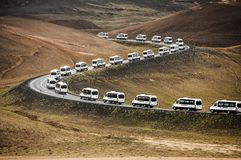 Les fourgons de bus touristique sur une route incurvée menant par une montagne aménagent en parc en Islande Photographie stock