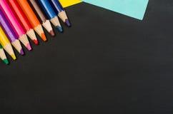 Les fournitures scolaires encadrent au fond noir de tableau Photographie de vue supérieure image stock