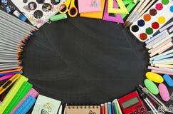 Les fournitures scolaires encadrent sur un fond de tableau Image libre de droits