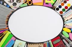 Les fournitures scolaires encadrent sur un fond de tableau Images stock