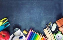 Les fournitures scolaires sur le fond noir de conseil vident l'espace de copie Photos libres de droits