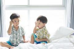 Les frères écoutent la chanson avec le téléphone portable pendant le matin sur le lit photo stock