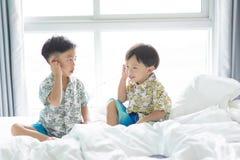 Les frères écoutent la chanson avec le téléphone portable pendant le matin sur le lit images libres de droits