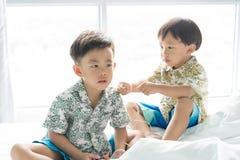 Les frères écoutent la chanson avec le téléphone portable pendant le matin sur le lit images stock
