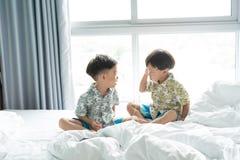 Les frères écoutent la chanson avec le téléphone portable pendant le matin sur le lit photographie stock libre de droits