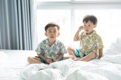 Les frères écoutent la chanson avec le téléphone portable pendant le matin sur le lit photos libres de droits