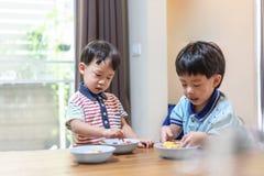 Les frères apprécient leur omelette préférée avant d'aller instruire photo stock