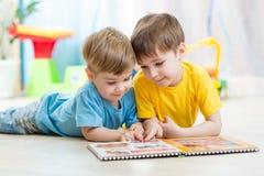 Les frères d'enfants ont lu un livre à la maison Images stock