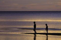 Les frères d'OE apprécient sur la plage avec la mer colorée dans le lever de soleil Image stock