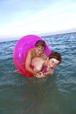 Les frères dans une boucle de bain ont l'amusement dans l'océan Photos stock