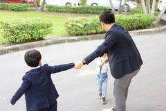 Les frères essayent de prendre leur père pour jouer avec eux au Th photo stock