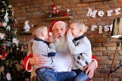 Les frères heureux de garçons chuchotent simultanément dans l'oreille de Noël Image stock