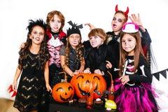 Les frères heureux et deux soeurs Halloween font la fête Photographie stock libre de droits
